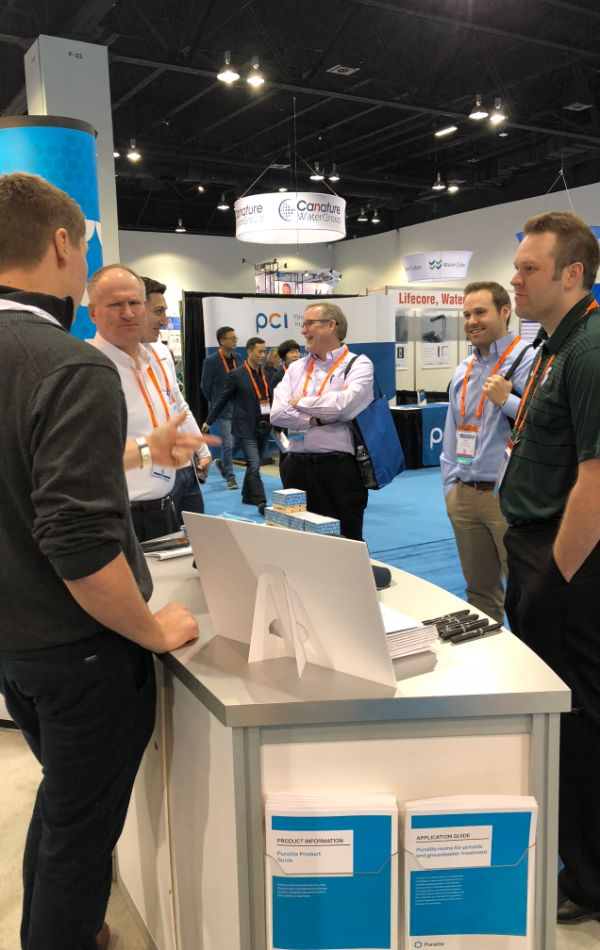 Speaking with attendees at the Puroltie WQA booth desk